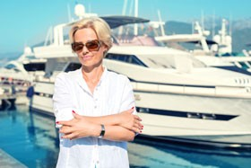 Proud Woman in Front of Her Yacht