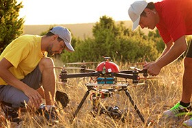 Men Setting Up Drone Before Flight