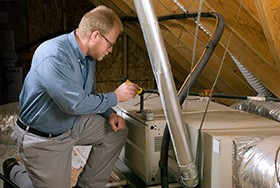 HVAC Contractor Inspects Furnace